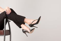 Girl in elegant trousers and high-heeled shoes. Girl with slim legs lying in armchair against white background stock images