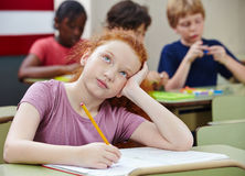 Girl in elementary school class. Pensive girl in elementary school class thinking and writing Royalty Free Stock Photography
