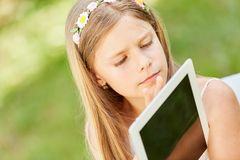 Girl learns how to use Tablet PC. Girl in elementary school learns how to use tablet pc and social media Royalty Free Stock Photography