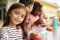 Girl at elementary school lunch table smiling to camera royalty free stock images