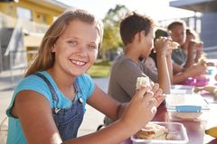 Girl at elementary school lunch table smiling to camera royalty free stock image