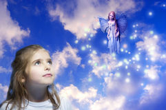 Girl and elf fairy. A girl with a beautiful elf fairy over beautiful cloudy sky with lights like a concept for dreams, imgination, child world and belief Royalty Free Stock Photo
