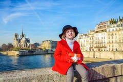 Girl on embankment near Notre Dame de Paris with Christmas gift. Bright in Paris. Portrait of stylish girl in red coat on embankment near Notre Dame de Paris in Royalty Free Stock Images