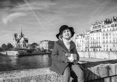 Girl on embankment near Notre Dame de Paris with Christmas gift. Bright in Paris. Portrait of stylish girl in red coat on embankment near Notre Dame de Paris in Stock Photos