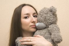 Girl embraces a bear Stock Images