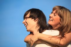 Girl embraces guy behind against sky Royalty Free Stock Photo