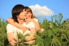 Girl embraces guy behind for among a grass Royalty Free Stock Photo