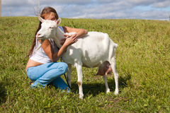 Girl embraces a white goat Stock Photo