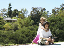 Girl (6-8) embracing brother in park, boy (10-12) sitting with skateboard, smiling, portrait Royalty Free Stock Photography