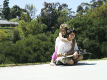 Girl (6-8) embracing brother in park, boy (10-12) sitting with skateboard, smiling, portrait Stock Photo