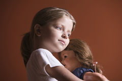 Girl Embracing Doll Stock Images