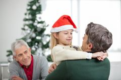Girl Embracing Father During Christmas. Girl embracing father with grandfather looking at them during Christmas at home Royalty Free Stock Photos