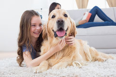 Girl embracing Golden Retriever while lying on rug Stock Image