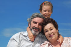 Girl embracing grandparents from back and smiling Royalty Free Stock Photo