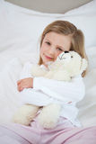 Girl embracing her teddy on the bed Stock Photos