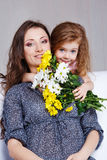Girl embracing mom Stock Images