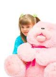 Girl embracing a pink bear Stock Photos