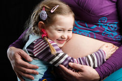 Girl embracing pregnant belly Royalty Free Stock Image