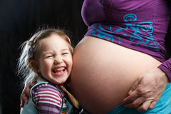 Girl embracing pregnant mother Stock Images