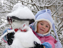 A girl embracing a snowman royalty free stock images