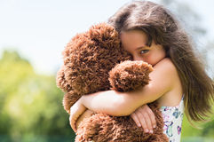 Girl embracing teddy bear. Cute little girl embracing her new teddy bear and looking at camera. Portrait of lovely female child with her peluche outdoor. Little Stock Images