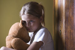 Girl embracing teddy bear in home Royalty Free Stock Photography