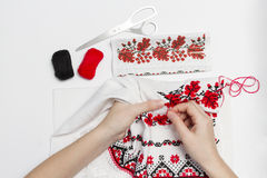 Girl embroider pattern on a towel close-up. Woman embroiders national pattern red thread on a towel Stock Photo