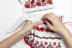 Girl embroider pattern on the towel. Woman embroiders national pattern red thread on a towel Stock Photography