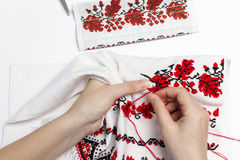 Girl embroider pattern on the towel. Woman embroiders national pattern red thread on a towel Stock Images