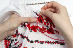 Girl embroider pattern on the towel. Woman embroiders national pattern red thread on a towel Royalty Free Stock Images