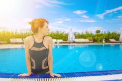 The girl emerges from the pool. stock photos