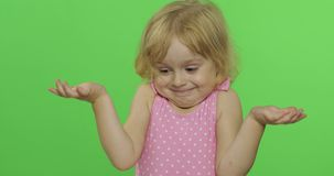 Girl emotionally makes faces and shows a hand gesture that she doesn`t know. Pretty girl emotionally makes faces and shows a hand gesture that she doesn`t know stock video footage