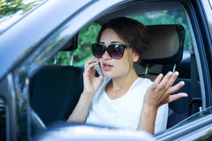 Girl emotionally speaks on the phone while driving Stock Images