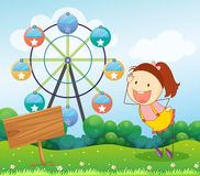 A girl beside an empty board with a ferris wheel at the back Royalty Free Stock Photography