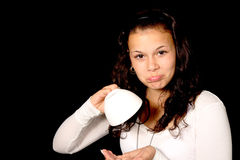 Girl with empty cup. Young woman with an empty cup on black background Royalty Free Stock Photography