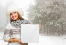 Girl with empty poster at winter forest Stock Photos