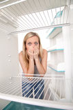 Girl and empty refrigerator Stock Images