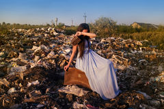 A girl with an empty wallet sits on a suitcase among the garbage dump and cries Stock Image