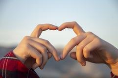 Girl&en x27; s-händer viks i formen av en hjärta arkivfoton