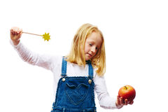 Girl enchant a apple. Girl enchants an apple to a frog Royalty Free Stock Photos