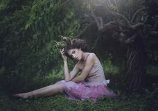 Girl enchanted Princess with horns sitting under a tree. Girl Mystical creature fawn in shabby clothes in a fairy forest royalty free stock photography