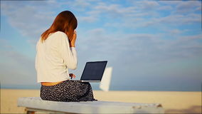 Girl ends a phone conversation while working with a laptop on the beach stock footage