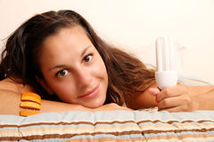 Girl with a energy saver light bulb Stock Image
