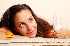 Girl with a energy saver light bulb. Young girl with a energy saver light bulb stock photo