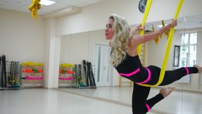 The girl is engaged in Aero yoga in the white Studio flying over the floor on the canvases in slow motion.  stock video