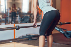 Girl engaged in with a bar in the gym. Deadlift Stock Images