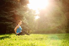 Girl is engaged in fitness in the park, doing exercises. Training on the street in the summer morning. Concept sport healthy stock images