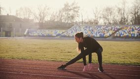 The girl is engaged in fitness at the stadium. Young girl, with long hair, brunette, in tight sportswear, performs fitness exercises at the stadium, the sun`s stock video