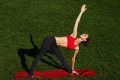 Girl is engaged in gymnastics on the red carpet on a sunny day. Woman practices yoga in nature Stock Image