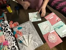 The girl is engaged in making greeting cards at home. Using paper, lace, braid and other materials. The girl is engaged in making greeting cards at home. Using Royalty Free Stock Photo